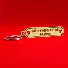 Nyckelring i trä med graverad text – KÖR FÖRSIKTIGT PAPPA